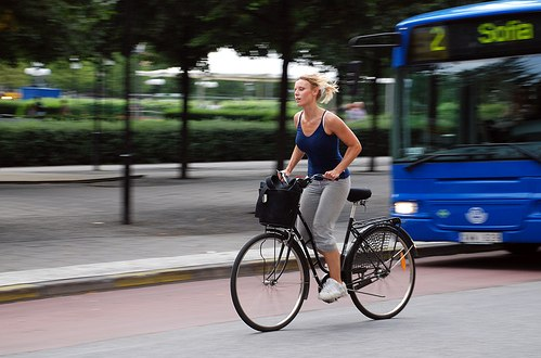 A woman pedals a bike ahead of a bus in Sweden, where 62 percent of people use active transportation. Photo by <a href=