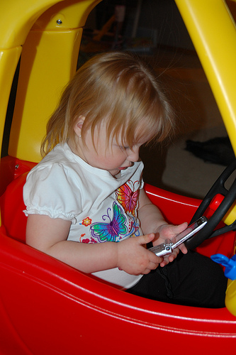 Texting and driving do not mix. This child should know better. Flickr photo by bsimser