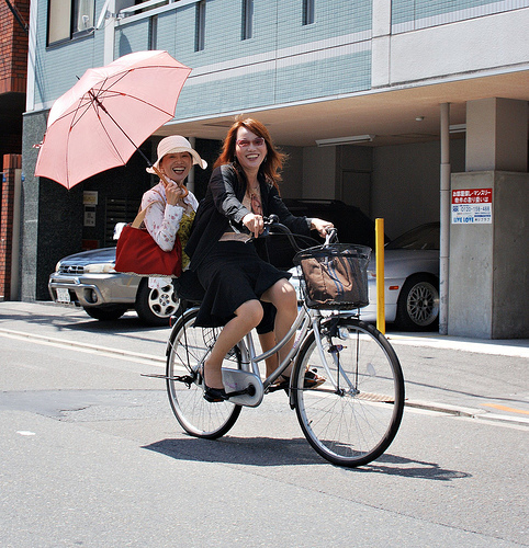 Two office workers biking in Osaka. Flickr photo by JanneM.