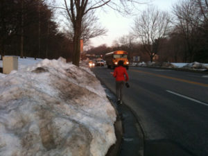 Snow removal priorities are called into question when students must walk to school in the road two weeks after the snowstorms.  Photo: WTOP.