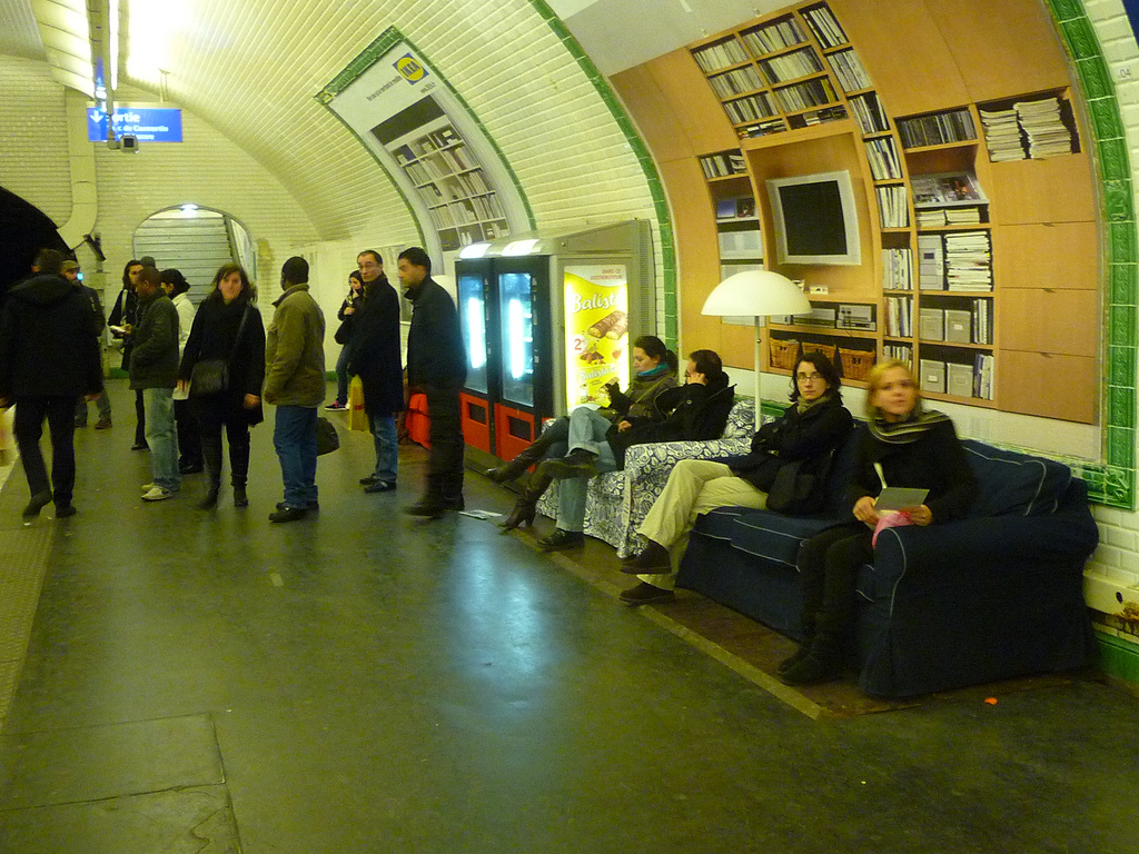 Transit riders relax in a living Ikea ad in the Paris Metro.  Source: pterjan.