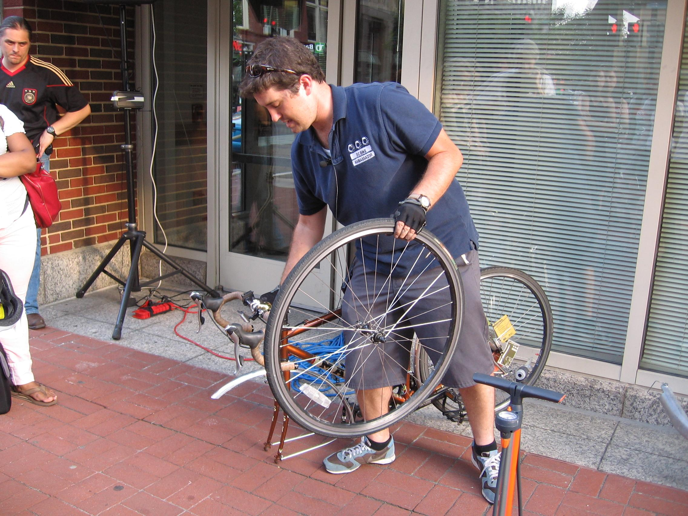 D.C. Bike Ambassador Daniel Hoagland demonstrates how to change a bike tire. Photo via Sylvia Blume.