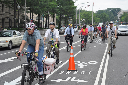 D.C. officials celebrated the opening of new bike lanes on Pennsylvania Avenue this week. The lanes would be safer if they were painted green and physically separated along the entire route. Photo via Transportation for America.