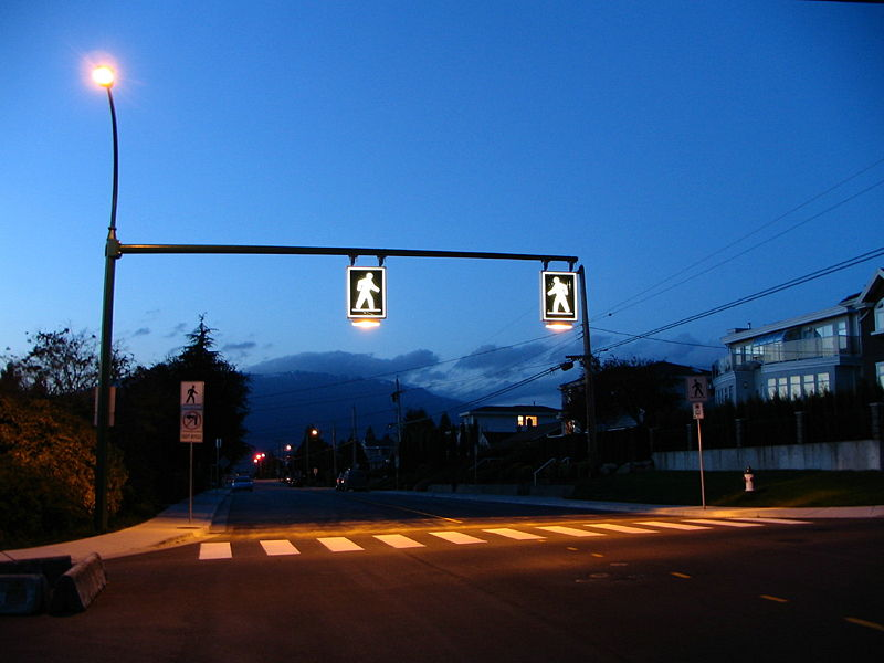 A zebra crosswalk in Burnaby, BC, Canada is enhanced with lit overhead signs. Photo via wikimedia.org.