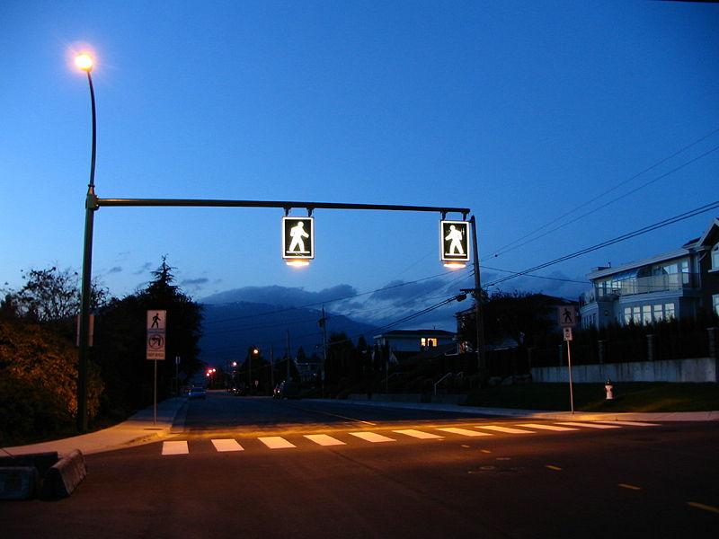 A zebra crosswalk in Burnaby, BC, Canada is enhanced with lit overhead signs. Photo via wikimedia.org.