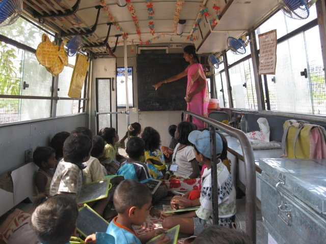 A teacher instructs students inside a classroom that is also a bus. The project, called School on Wheels, was developed by Door Step School. Photo courtesy of doorstepschool.org