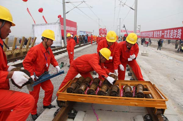 Workers laying the last track of China's new highspeed rail system. Photo via The People's Daily.