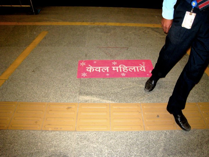 "A sign reading ""women only"" in Hindi on the platform of the Delhi Metro. Photo by Erica Schlaikjer."