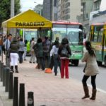 Public transit users wait at a bus stop on Bogotá's Carrera Séptima.  As part of the reorganization of the city's transit under the Integrated Public Transport System (SITP), more than 1,500 new bus stops will be installed, including both permanent shelters and movable flag stations like the one above. Photo by Gwen Kash.