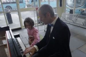 Pianist Andy Jackson leads a young musician in Beethoven's Moonlight Sonata at Haymarket Bus Terminal. Photo courtesy of Arts Council England.