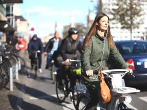 "A passenger navigates Copenhagen's streets on one of the new ""smart bikes"". Gobike, Copenhagen's new public shared bicycle scheme, is the first bikeshare system to integrate intelligent transport system (ITS) elements into its design. Photo courtesy of Gobike."