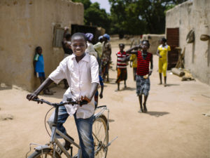 A boy rides a bicycle in Zorro, Burkina Faso, while friends look on. Transforming Transportation 2014 (#TTDC14) will examine sustainable solutions to the challenges of urban mobility in developing world countries like Burkina Faso. Photo by Ollivier Girard/CIFOR. Cropped.