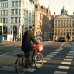 A woman bikes in one of Amsterdam's bicycle lanes. The dominance of bike lanes in the city has been the result of community activism and human-centered policy decisions.