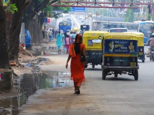 A woman walks among motorized traffic in Bangalore, India. Pedestrian rights are often ignored across India due to a lack in legal provisions for pedestrians, forcing them to walk alongside fast moving traffic at great risk to their lives. Photo by jchessma/Flickr. Cropped.