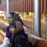 Mother and daughter wait for Ahmedabad, India's bus rapid transit (BRT) system, the Janmarg. Photo by Meena Kadri/Flickr. Cropped.