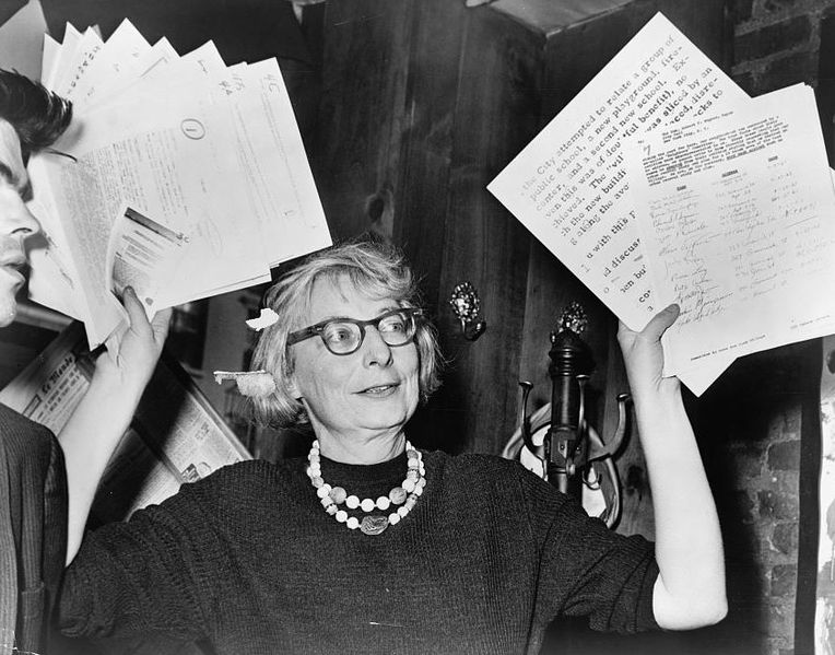 Jane Jacobs holds up petitions and documentary evidence at one of many meetings to save the West Village from the motor vehicle. Photo by Wikimedia.