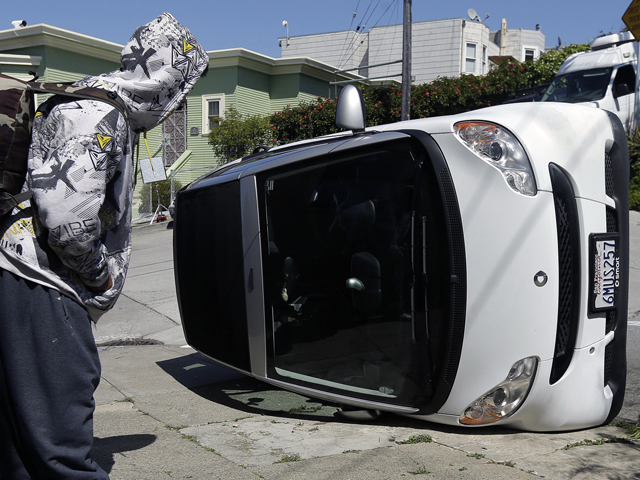 Smart car tipped in San Francisco, California. Photo by Jeff Chiu.