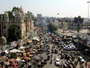 Pedestrians, personal vehicles, and pedestrians struggle to coexist on a busy street in Hyderabad, India.