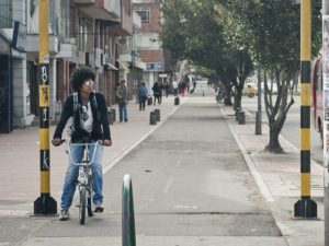 A man rides a bike in Bogota, Colombia. Sustaining a dialogue with the local community about local needs should be a priority for Habitat III's New Urban Agenda. Photo by Juan Felipe Rubio/Flickr.