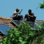 Two men in Bosnia and Herzegovina install solar panels on their roof. Photo by UNDP in Europe and Central Asia / Flickr