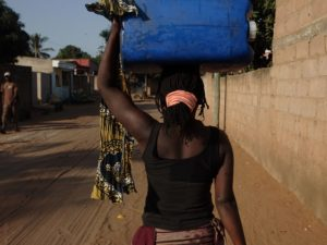 A woman carries water home in urban Mozambique. Photo by: John Hogg / World Bank / Flickr